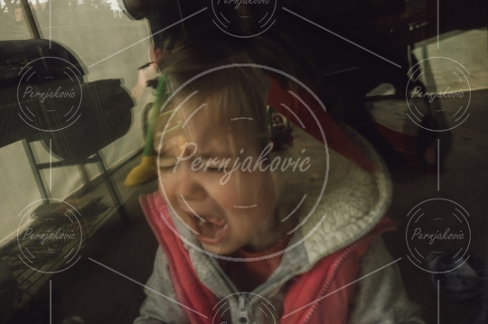 Sad baby girl crying and yelling behind a glass door