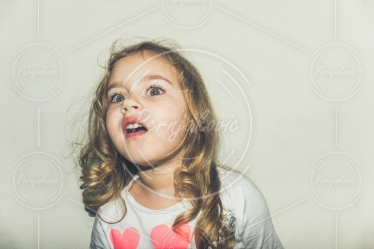 Portrait of a beautiful young girl with magic eyes looking surprised