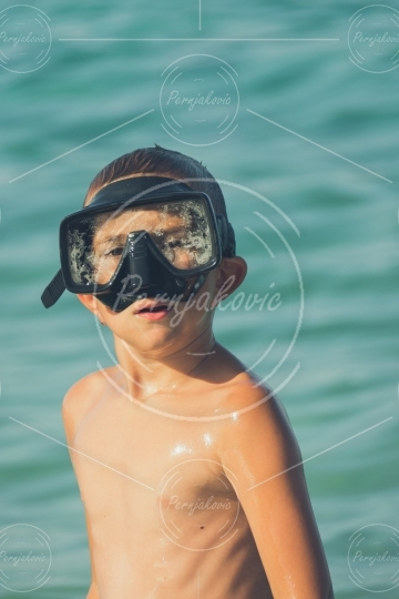 Boy in sea water with scuba mask