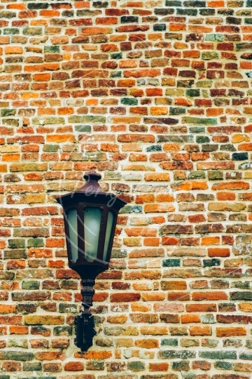 Brick wall with old metal lamp